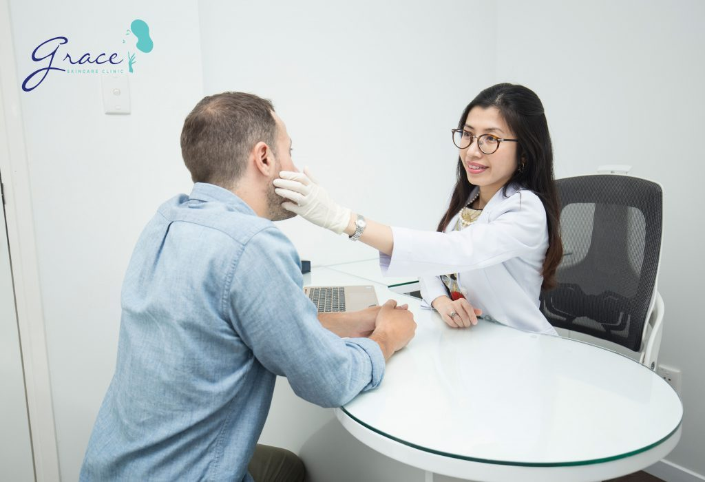 Bác sĩ da liễu phòng khám thảo luận cách khắc phục rụng tóc với khách hàng